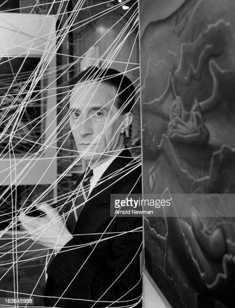Portrait of Frenchborn artist Marcel Duchamp seen behind a small section of his 'Sixteen Miles of String' installation part of the 'First Papers of...