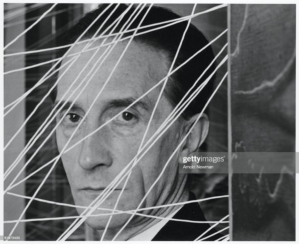 Portrait of French-born artist <a gi-track='captionPersonalityLinkClicked' href=/galleries/search?phrase=Marcel+Duchamp&family=editorial&specificpeople=227454 ng-click='$event.stopPropagation()'>Marcel Duchamp</a> (1887 - 1968), seen behind a small section of his 'Sixteen Miles of String' installation, part of the 'First Papers of Surrealism' exhibition at the Whitelaw Reid mansion, New York, New York, 1942.