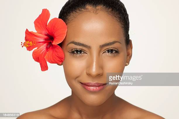 Portrait of fresh clear woman face with hibiscus flower.