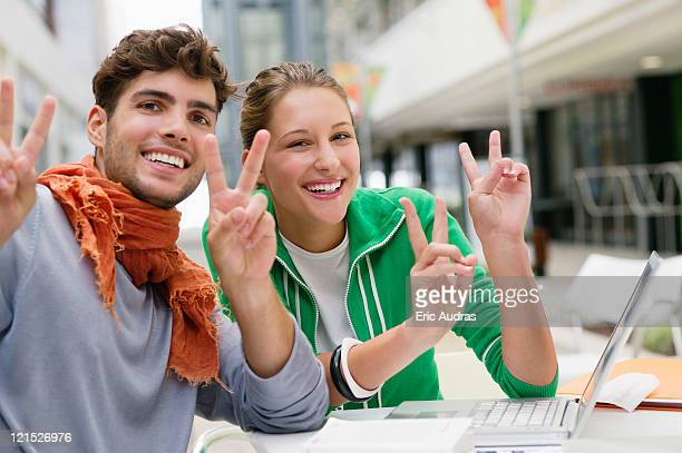 Portrait of friends gesturing peace while using laptop