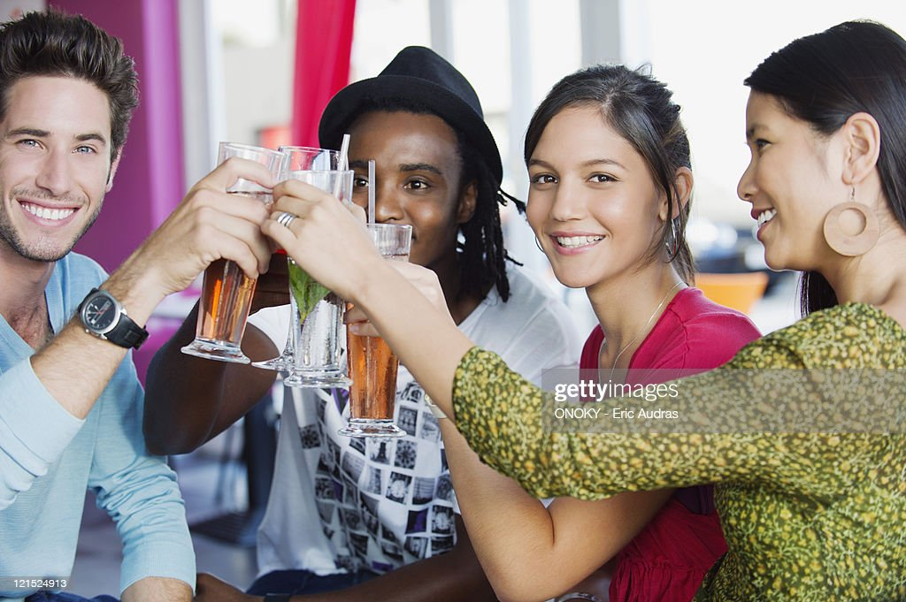 Portrait of friends toasting drinks in a restaurant : Stock Photo
