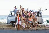 Portrait of friends with van on beach