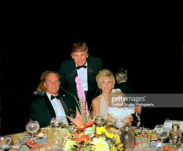 Portrait of from left sports broadcaster former football player Frank Gifford and married couple real estate developer Donald Trump and Marla Maples...