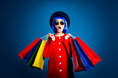 Portrait of frustrated astonishd woman in red coat holding colorful packets in hands having wide open mouth problem  isolated on blue background with shadow and light