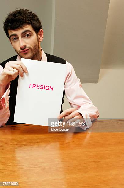 portrait of frustrated businessman sitting at desk holding resign document