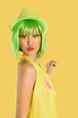 Portrait of funky young woman with green hair puckering her lips against yellow background
