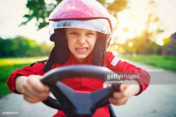 Porträt von wütend kleine Junge auf einem schnell go-kart-Fahren.