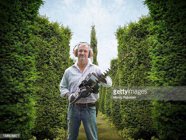 Portrait of gardener wearing ear protectors and visor holding hedge trimmer