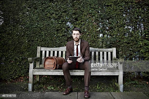 Portrait of gentleman sitting on bench with iPad