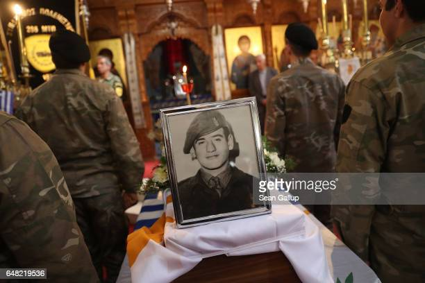 A portrait of Georgiou Theodoulos Theodoulou stands on the small coffin that contains his remains at his Orthodox funeral service on March 5 2017 in...