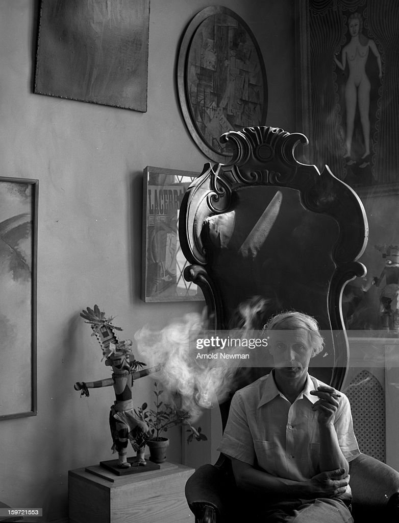 Portrait of German painter <a gi-track='captionPersonalityLinkClicked' href=/galleries/search?phrase=Max+Ernst&family=editorial&specificpeople=932116 ng-click='$event.stopPropagation()'>Max Ernst</a> (1891 - 1976) as he sits in a high-backed chair, a cigarette in his hand, New York, 1942. Ernst, with his arms folded, is in front of several peice of sculpture in the house he shared with then-wife Peggy Guggenheim.