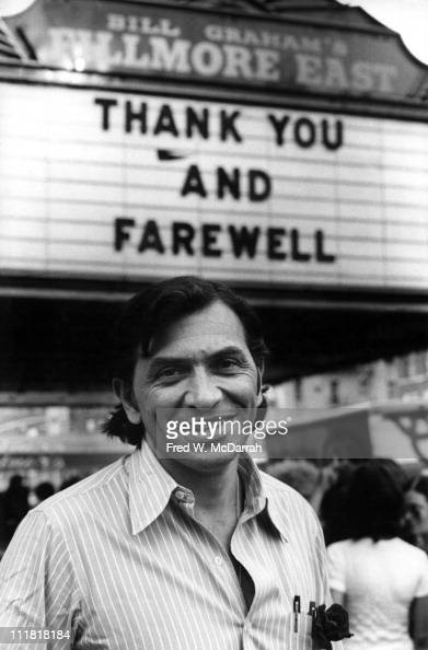 Portrait of Germanborn America concert promoter Bill Graham as smiles and poses under the marquee of his concert venue the Fillmore East on it's...