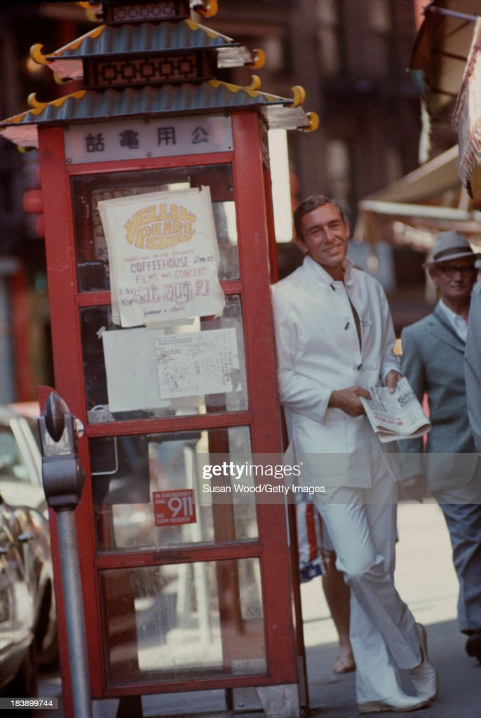 Portrait of German-born American fashion designer John Weitz (1912 - 2002) dressed in one of his designs, a white suit with toggle fasterners, as he poses beside a stylized phone booth, Manhattan's Chinatown, New York, New York, August 1971. The image was taken during a fashion shoot for New York magazine.