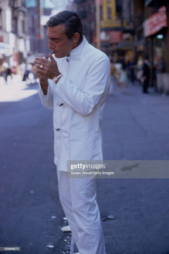 Portrait of German-born American fashion designer John Weitz (1912 - 2002) dressed in one of his designs, a white suit with toggle fasterners, as he lights a cigarette on the streets of Manhattan's Chinatown, New York, New York, August 1971. The image was taken during a fashion shoot for New York magazine.