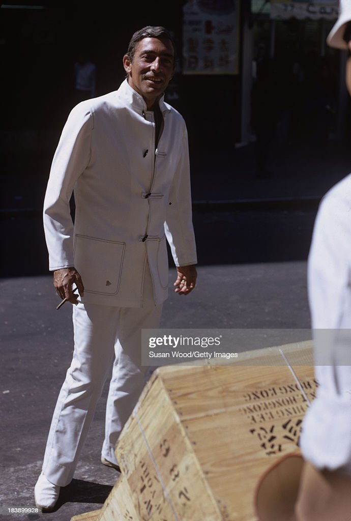 Portrait of German-born American fashion designer John Weitz (1912 - 2002) dressed in one of his designs, a white suit with toggle fasterners, as he poses on the streets of Manhattan's Chinatown, New York, New York, August 1971. The image was taken during a fashion shoot for New York magazine.