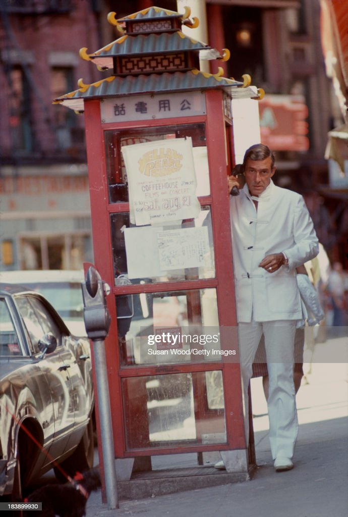 Portrait of German-born American fashion designer John Weitz (1912 - 2002) dressed in one of his designs, a white suit with toggle fasterners, as he makes a call from a stylized phone booth, Manhattan's Chinatown, New York, New York, August 1971. The image was taken during a fashion shoot for New York magazine.