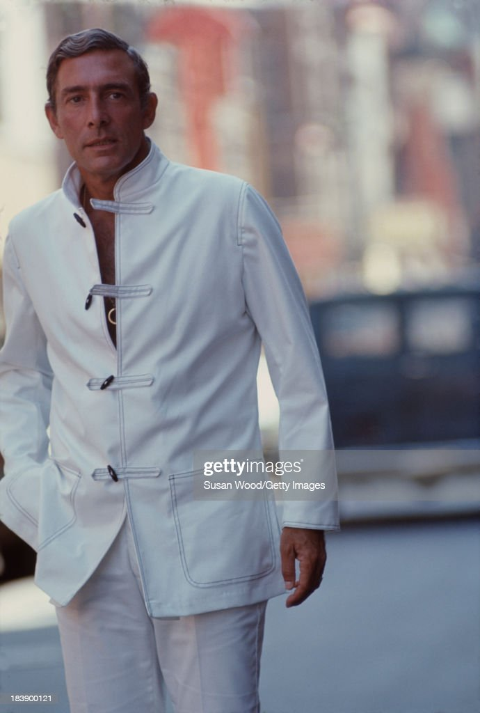 Portrait of German-born American fashion designer John Weitz (1912 - 2002) dressed in one of his designs, a white suit with toggle fasterners, as he walks on the streets of Manhattan's Chinatown, New York, New York, August 1971. The image was taken during a fashion shoot for New York magazine.