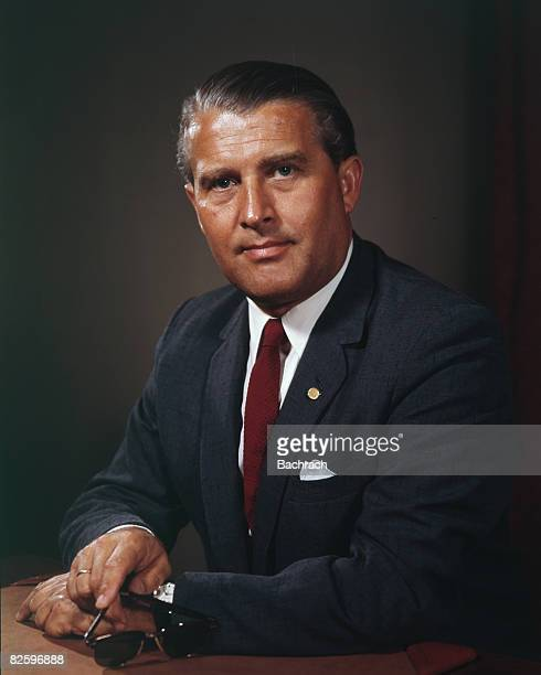 Portrait of Germanborn American rocket scientist Wernher von Braun as he sits at a desk a pair of sunglasses in one hand Washington DC 1962