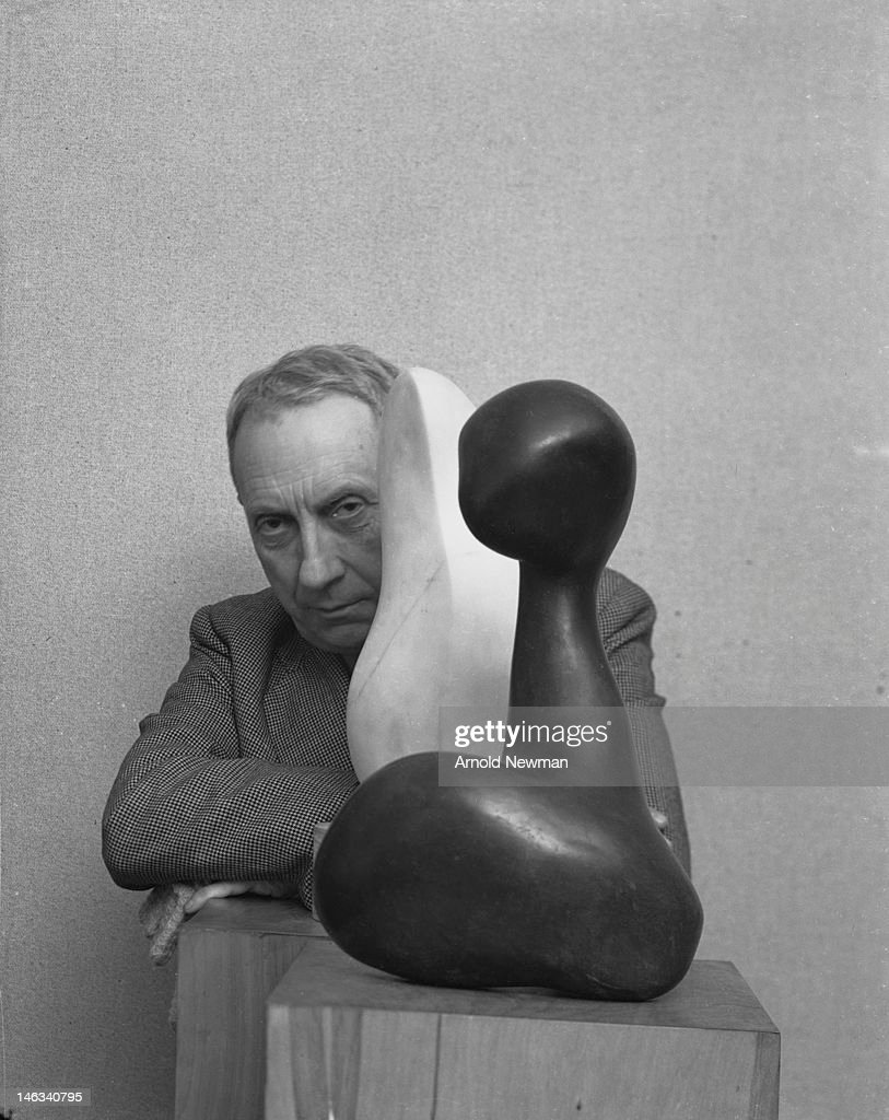 Portrait of German-French artist Jean Arp (1886 - 1966) as he poses with a sculpture, New York, New York, January 31, 1949.