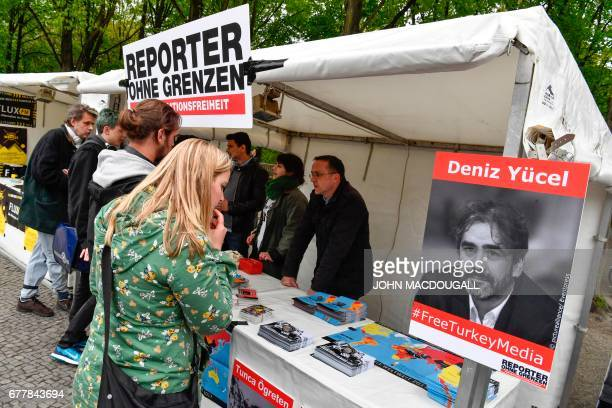A portrait of GermanTurkish journalist Deniz Yucel is on display at the 'Reporters without Borders' stand during a concert organised in front of...