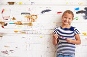 Portrait Of Girl Against Paint Covered Wall In Art Studio