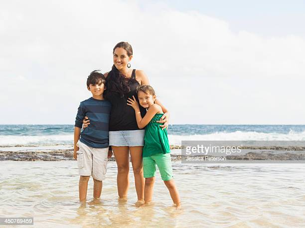 Portrait of girl (6-7) and boy (10-11) standing on beach with mother