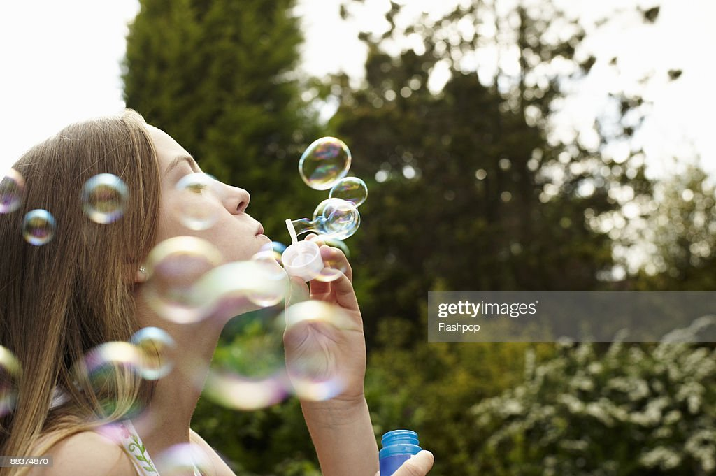 Portrait of girl blowing bubbles : Stock Photo
