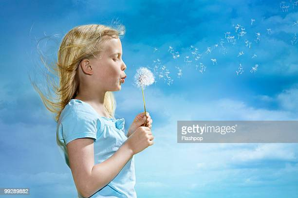 Portrait of girl blowing dandelion clock