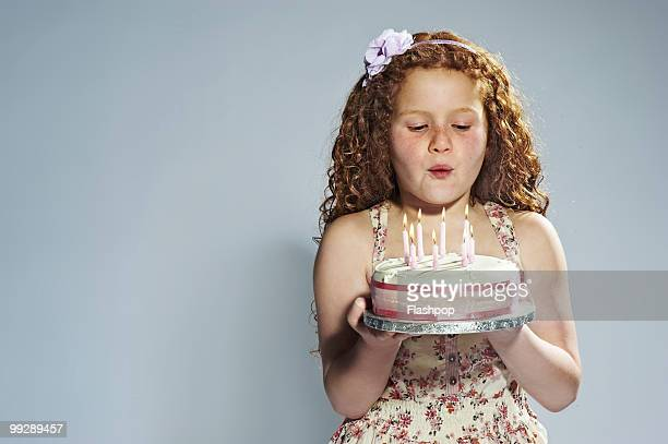 Portrait of girl blowing out candles on cake