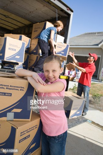 Portrait of girl (7-9) by truck of cardboard boxes : Stock-Foto
