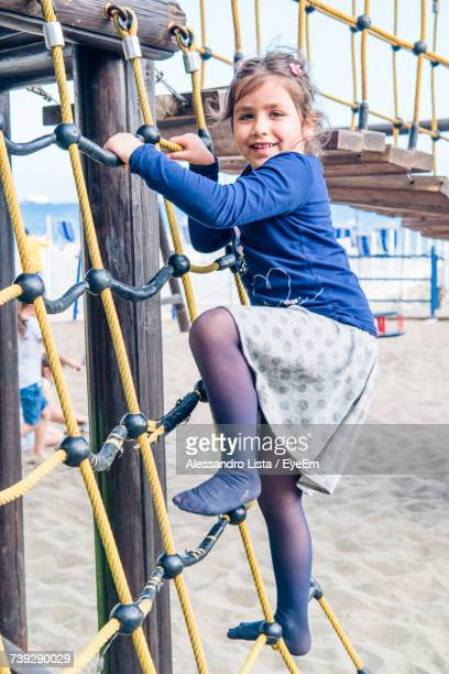 Portrait Of Girl Climbing On Jungle Gym At Playground