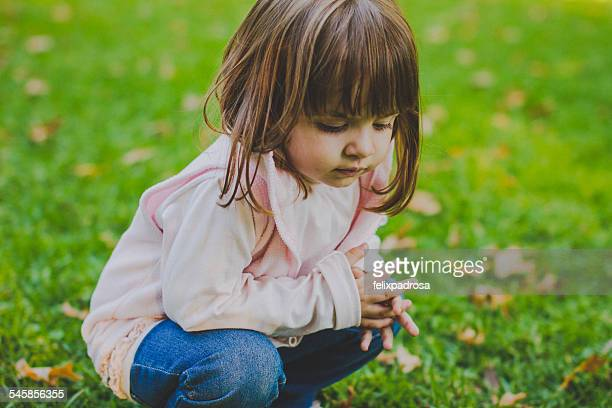 Portrait of girl (2-3) crouching on grass