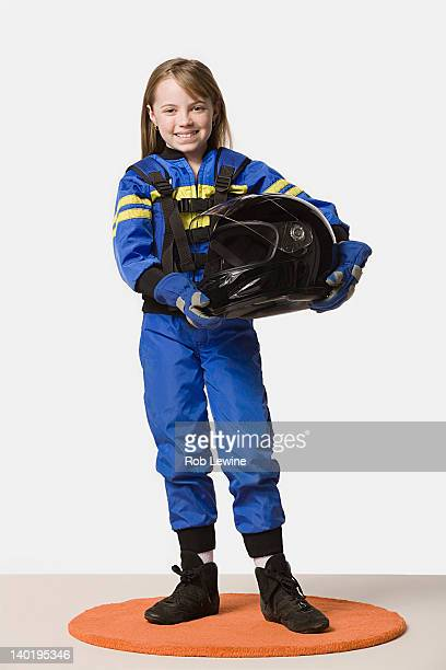 Portrait of girl (8-9) dressed as racing driver, studio shot