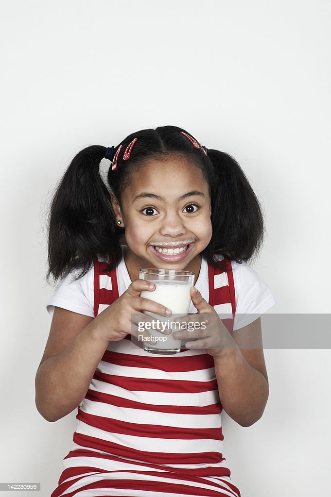 Portrait of girl drinking a glass of milk : Stock Photo