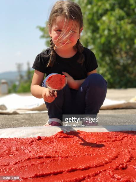 Portrait Of Girl Drying Tomato Puree Outdoors