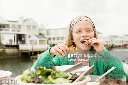 Portrait of girl (8-9) eating baguette and salad : Stock-Foto