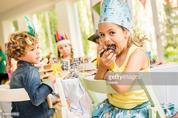Portrait of girl eating cake at kids birthday party