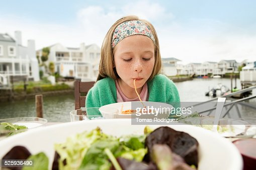 Portrait of girl (8-9) eating pasta : Photo