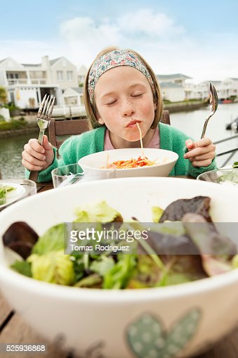 Portrait of girl (8-9) eating pasta : Stockfoto