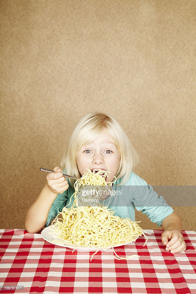 Portrait of girl eating spaghetti : Stock Photo
