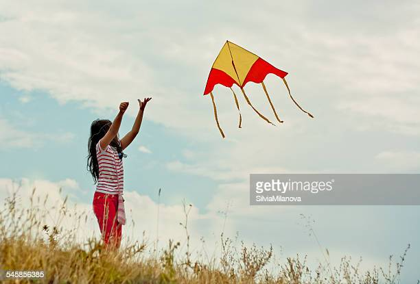 Portrait of girl (8-9) flying kite on hill