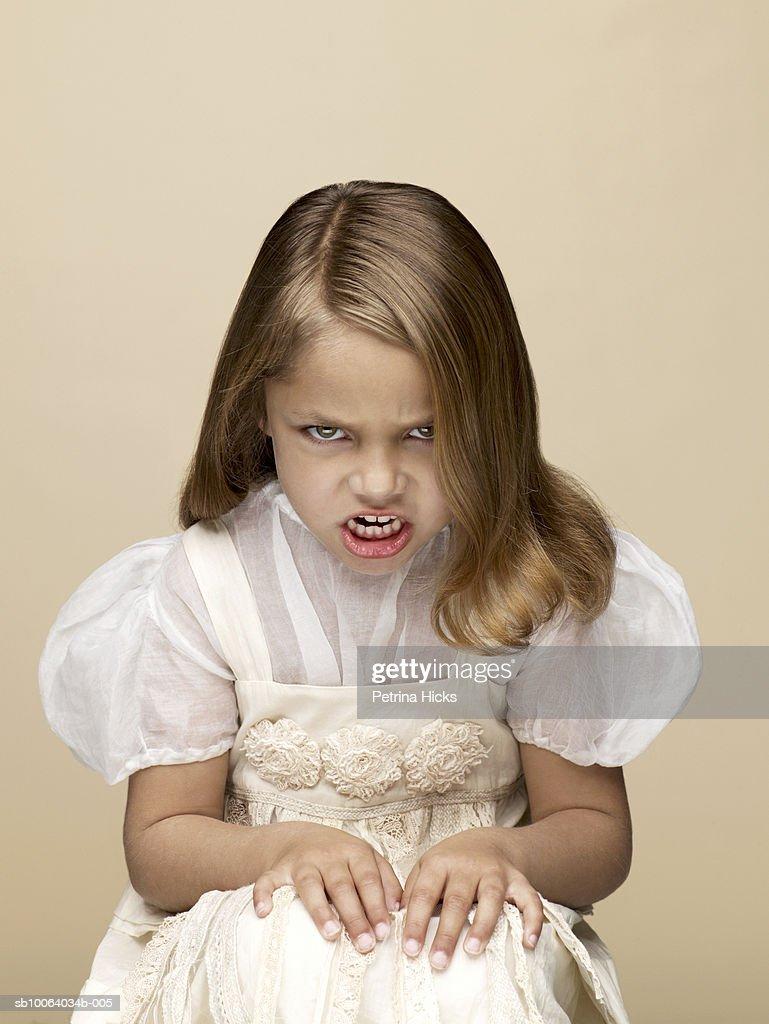Portrait of girl (4-5) growling, sitting in studio