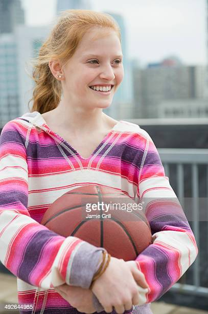 Portrait of girl (12-13) holding ball, Jersey City, New Jersey, USA