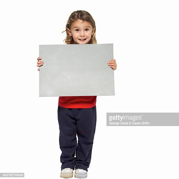 Portrait of girl (4-5) holding blank card