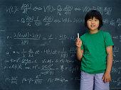 Portrait of girl holding chalk in front of chalkboard