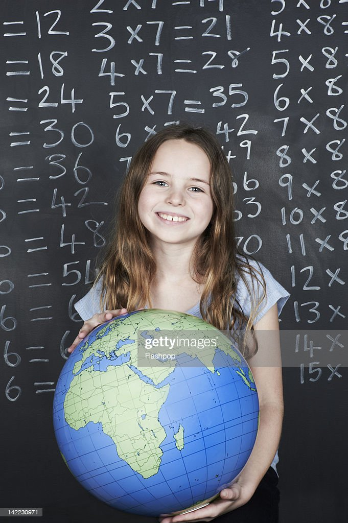 Portrait of girl holding globe in class : Stock Photo