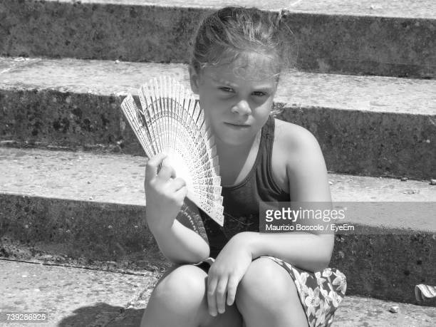 Portrait Of Girl Holding Hand Fan While Sitting On Staircase