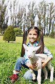 Portrait of girl (6-7) holding lamb