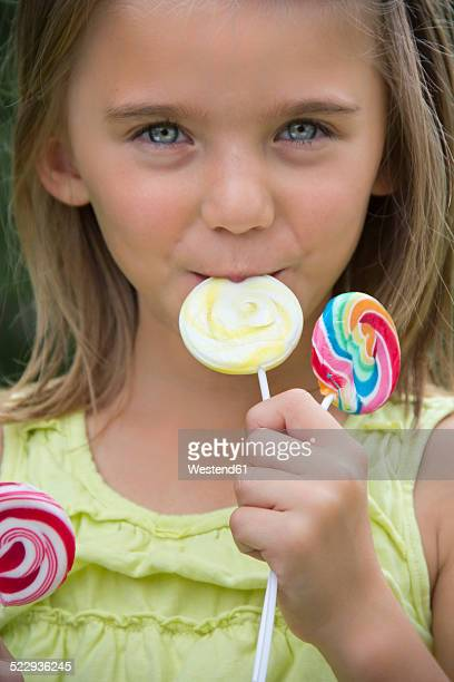 Portrait of girl holding lollipops