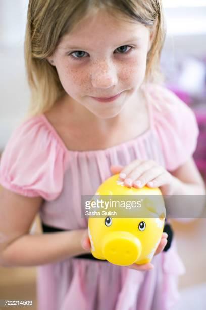 Portrait of girl holding piggy bank